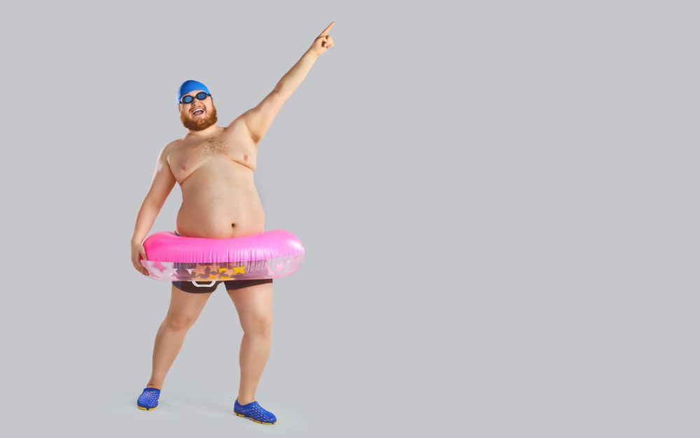 Fat,Funny,Man,In,Swimming,Trunks,With,An,Inflatable,Ring