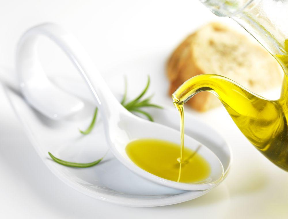Bottle,Pouring,Virgin,Olive,Oil,In,A,Porcelain,Spoon