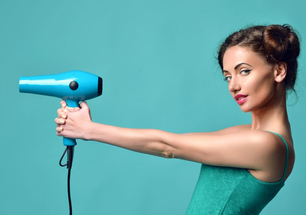 Happy,Young,Curly,Brunette,Woman,With,Hair,Dryer,On,Blue
